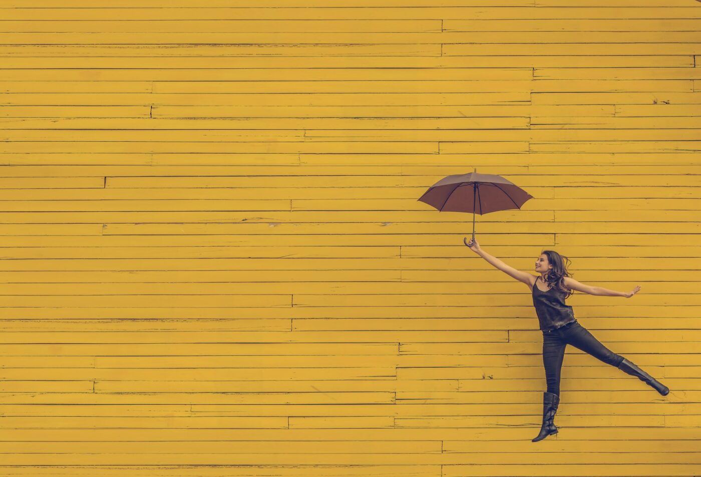 Lady hovering in air with open umbrella against a yellow brick wall