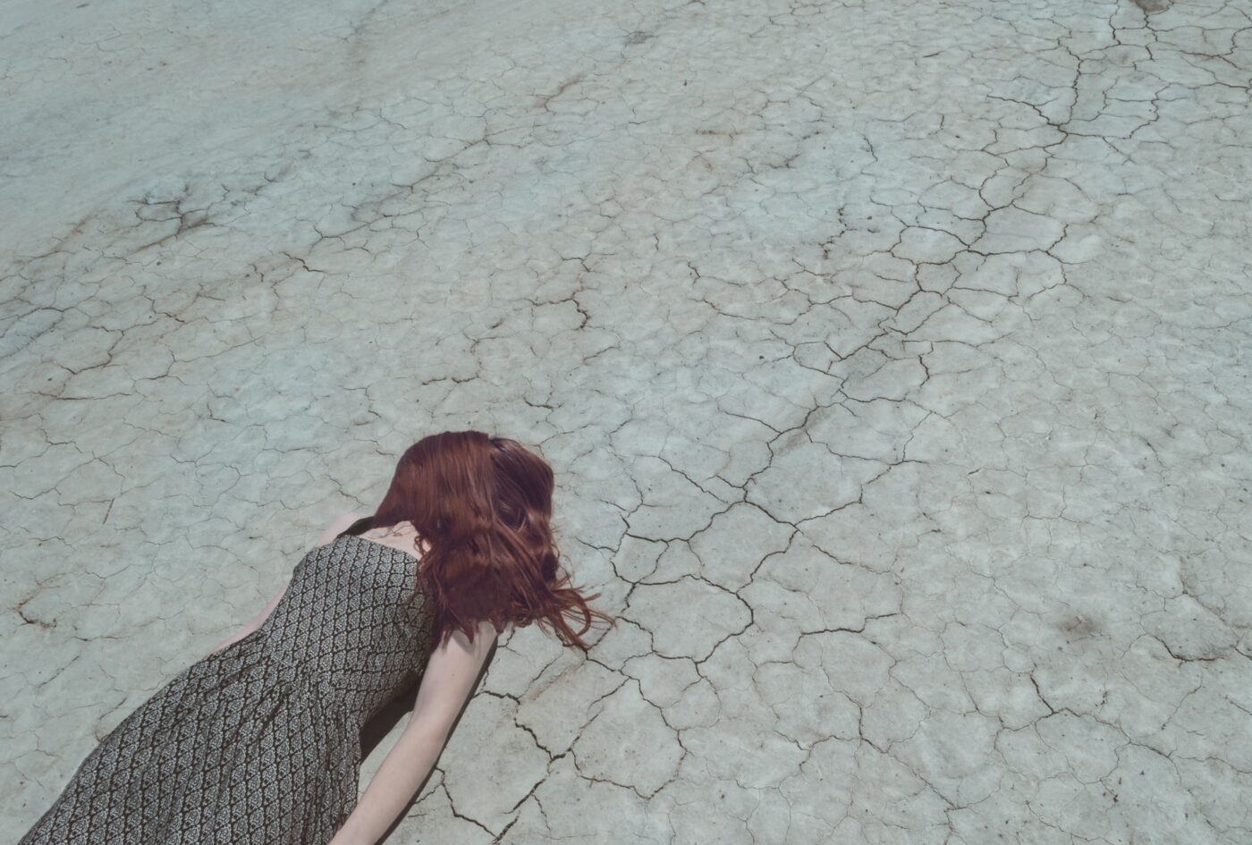 woman lying facedown on dry cracked outdoor surface